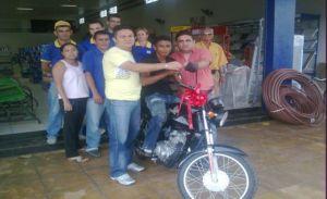 Os gerentes Gilson e Paulinho entregam a mota para o ganhador Pedro Alves